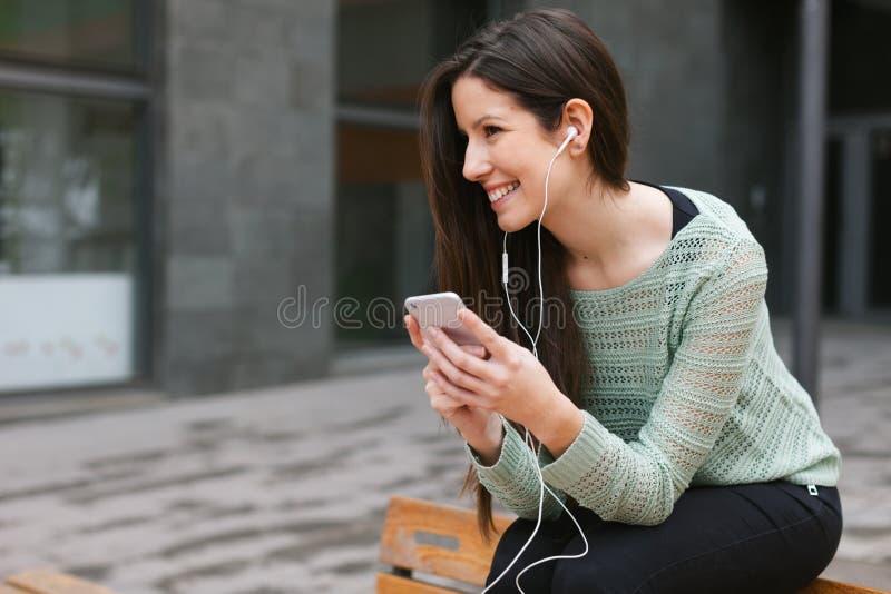 Молодая красивая женщина слушая к музыке с телефоном внутри outdoors стоковые фото
