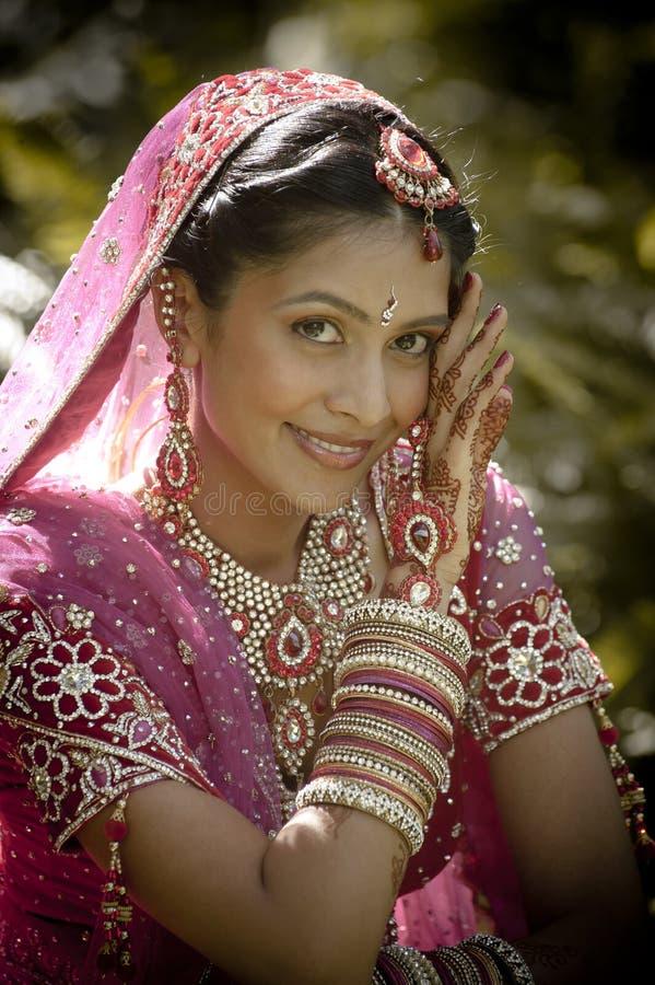 Молодая красивая индийская индусская невеста сидя в саде outdoors стоковое изображение rf