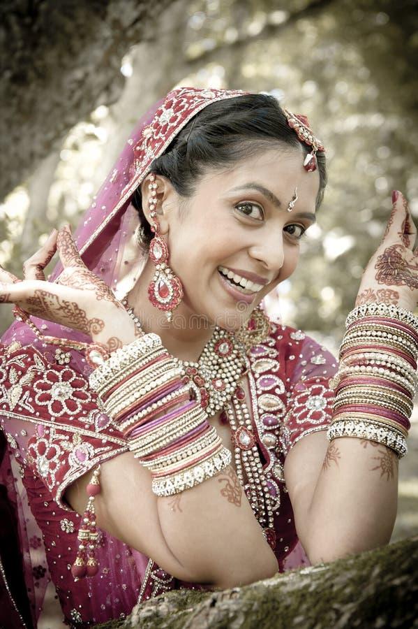 Молодая красивая индийская индусская невеста смеясь над под деревом при покрашенные поднятые руки стоковая фотография