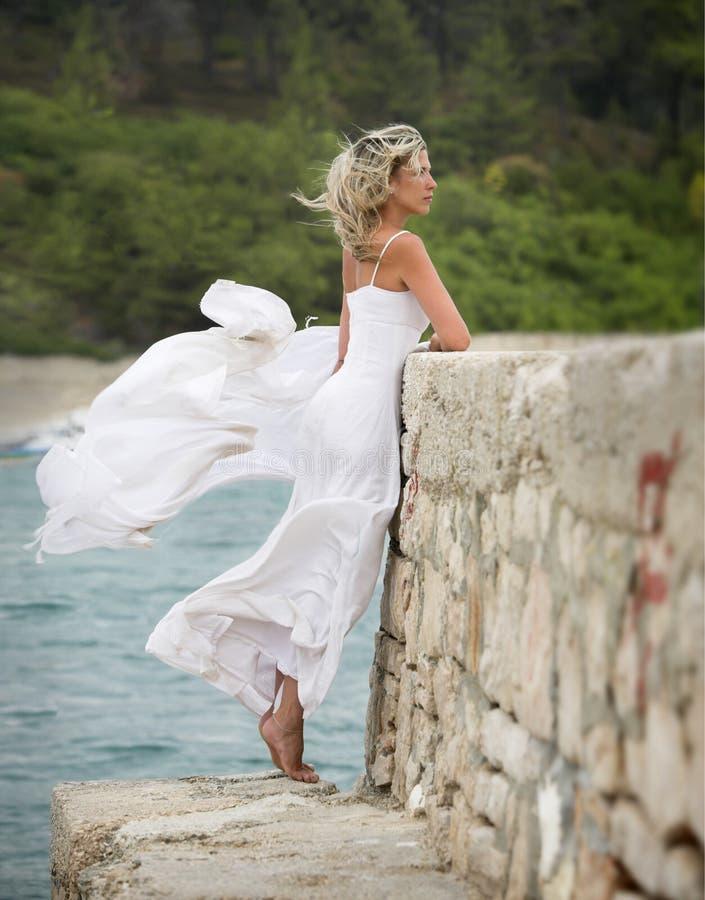 Молодая, красивая и сексуальная женщина, белое платье, ветер стоковые изображения