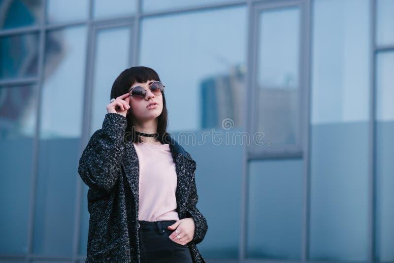 Молодая, красивая и стильная одетая девушка весной которая регулирует его стекла и представлять на городской предпосылке стоковая фотография