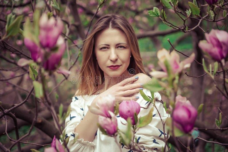 Молодая красивая кавказская женщина в зацветая саде весны магнолий Девушка в саде на пасмурный день стоковые изображения rf