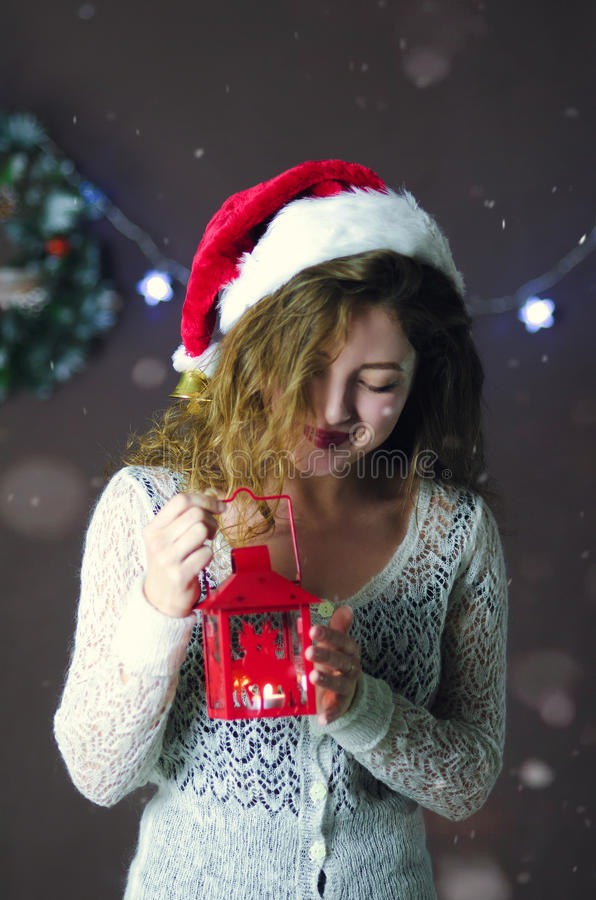 Молодая красивая милая девушка усмехаясь, стоя и держа фонарик в руке на предпосылке украшений рождества стоковая фотография rf