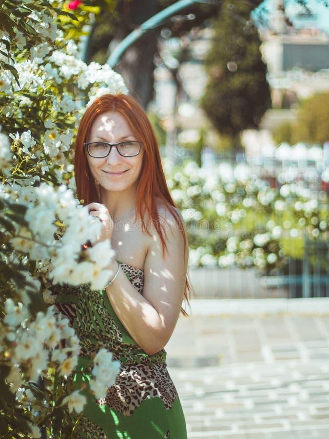 Молодая красивая милая женщина при красные волосы и стекла представляя в саде цветков, Roma, Италии стоковое фото