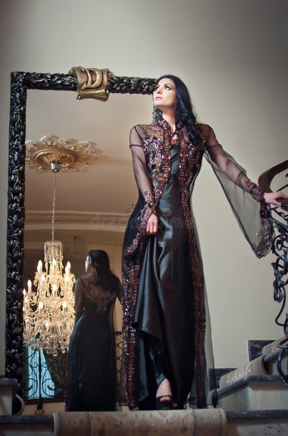 Молодая красивая роскошная женщина в длинном элегантном черном платье. Женщина брюнет с большим зеркалом в предпосылке. Обольстите стоковые фотографии rf