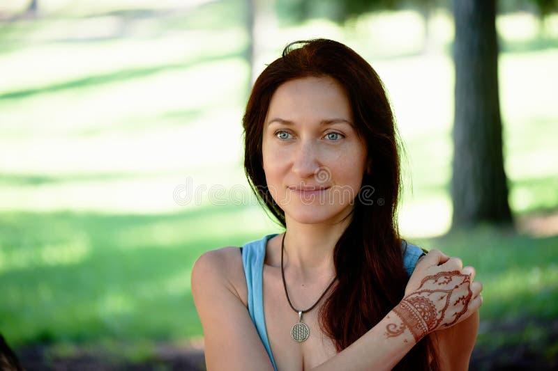 Молодая красивая рыжеволосая девушка делает йогу в парке на зеленой предпосылке стоковые изображения rf