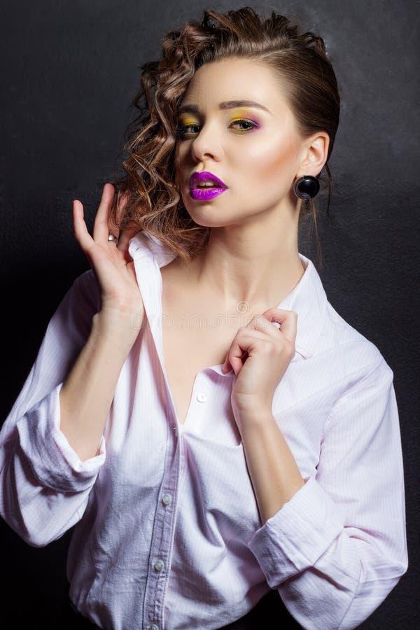Молодая красивая сексуальная девушка с ярким составом и красивые волосы в белой рубашке в студии на черной предпосылке стоковая фотография rf