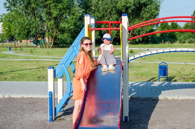 Молодая красивая семья ребёнка матери и дочери счастливая играя на качании, и езда в усмехаться парка атракционов стоковые фотографии rf