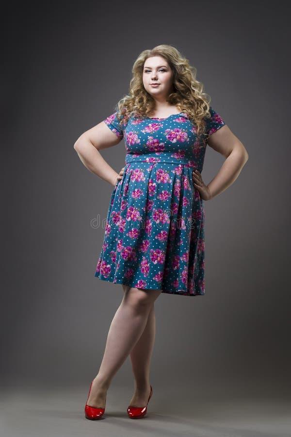 Молодая красивая счастливая блондинка плюс модель размера в платье и ботинках, женщине xxl на серой предпосылке студии стоковое изображение