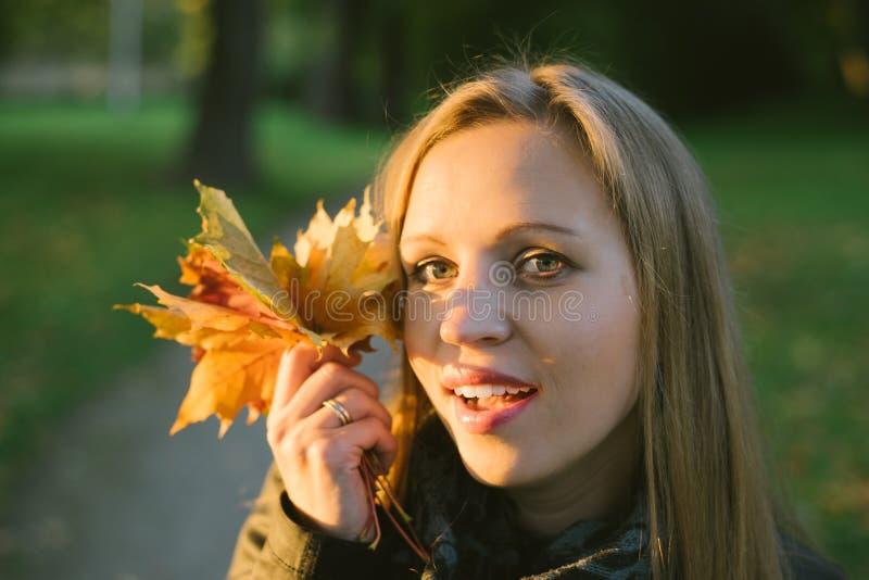 Молодая красивая усмехаясь дама осенним заходом солнца стоковые изображения