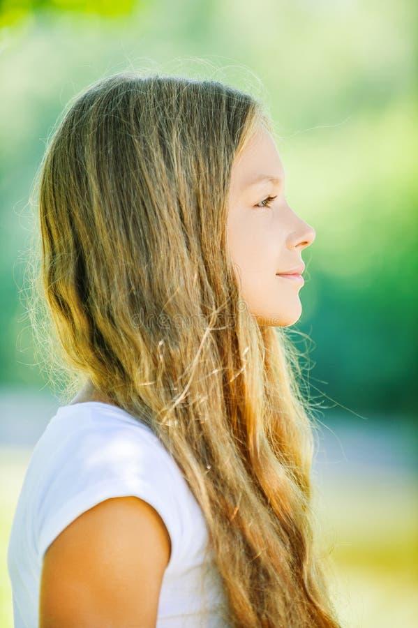Молодая красивая усмехаясь девушка в профиле стоковое изображение