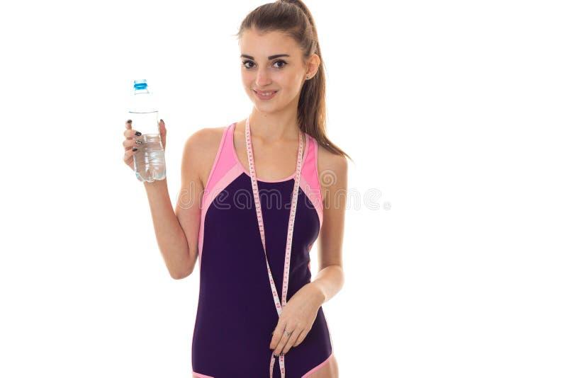 Молодая красивая худенькая девушка в купальном костюме тела держа бутылку воды и измеряя ленты на шеи стоковые изображения