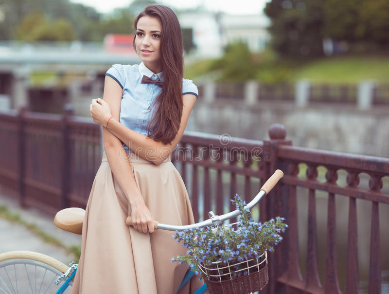 Молодая красивая, элегантно одетая женщина с велосипедом внешним стоковое фото rf