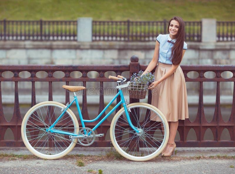 Молодая красивая, элегантно одетая женщина с велосипедом внешним стоковое изображение rf