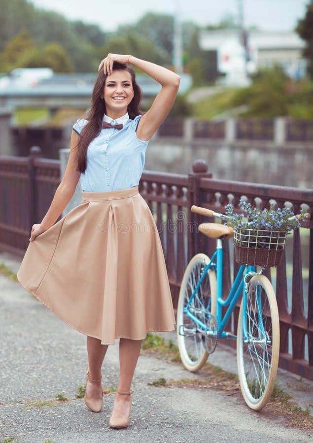 Молодая красивая, элегантно одетая женщина с велосипедом внешним стоковые фото