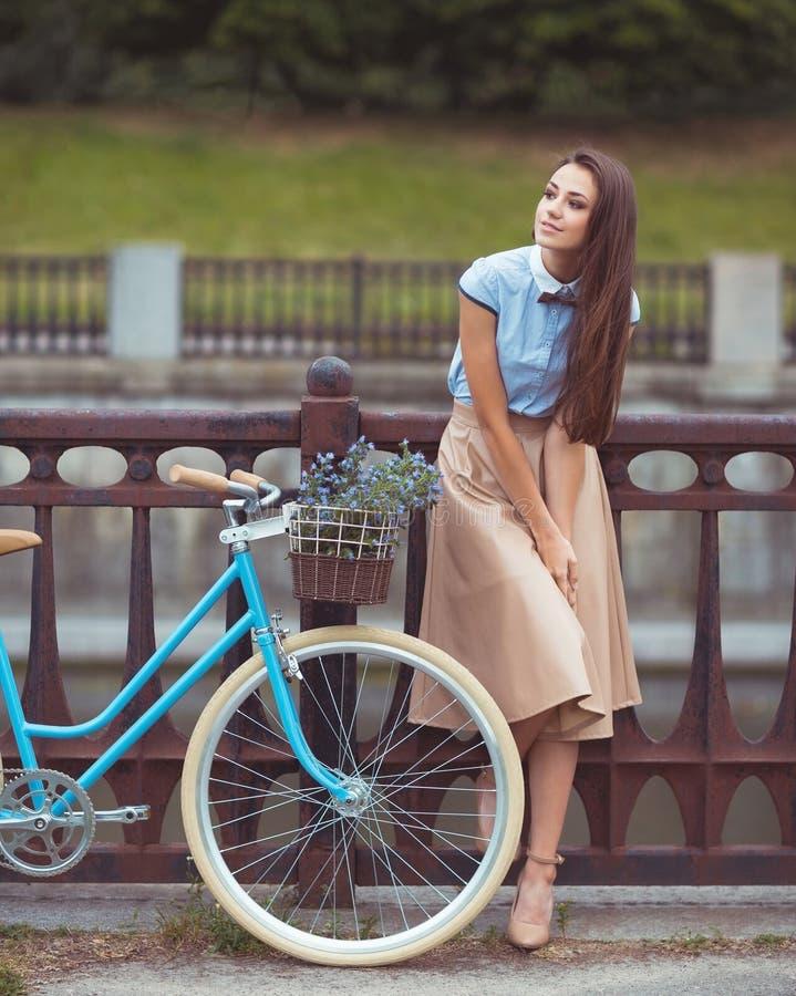 Молодая красивая, элегантно одетая женщина с велосипедом Красота, f стоковые фотографии rf