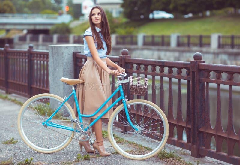 Молодая красивая, элегантно одетая женщина с велосипедом стоковые изображения