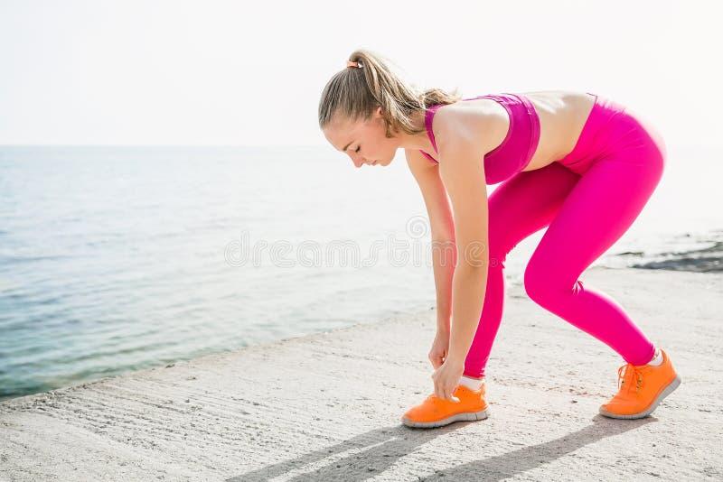 Молодая красивая sportive девушка в розовой форме на море стоковые фотографии rf