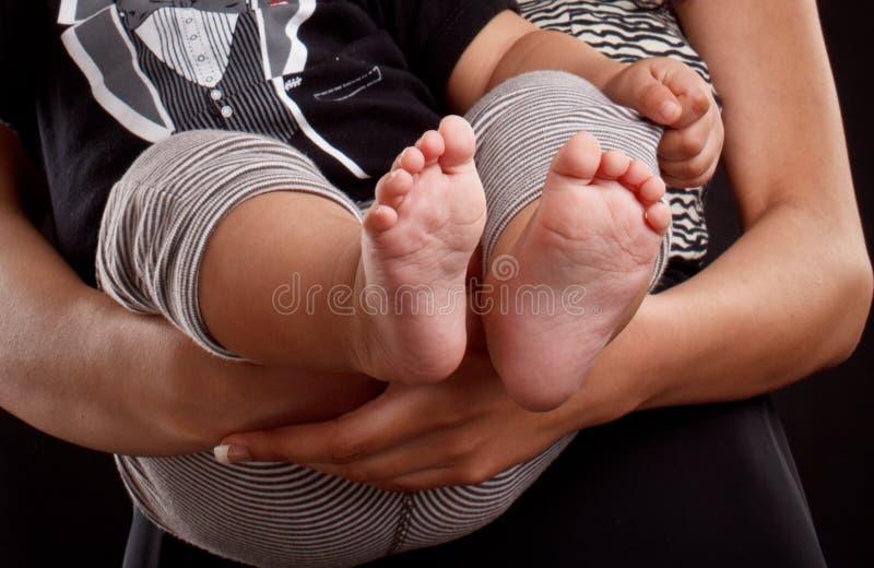 Молодая мама латиноамериканца держа ноги младенца стоковое фото