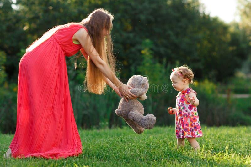 Молодая мать в взятиях платья носит маленькую дочь в парке стоковое фото rf