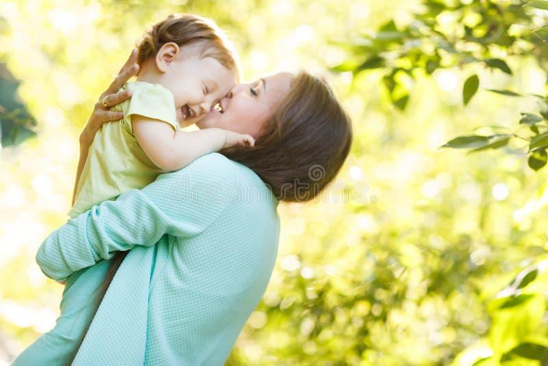 Молодая мать в парке держа дочь стоковое изображение rf
