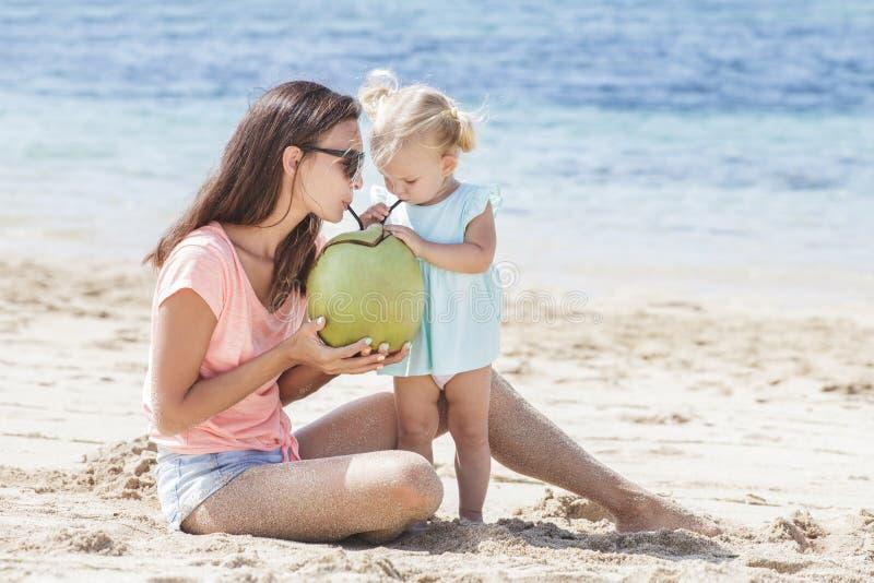 Молодая мать деля воду кокоса с ее маленьким whil дочери стоковое изображение