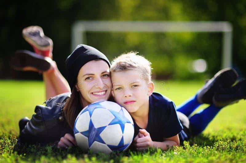 Молодая мать и ее мальчик играя игру футбола на солнечный летний день стоковая фотография rf