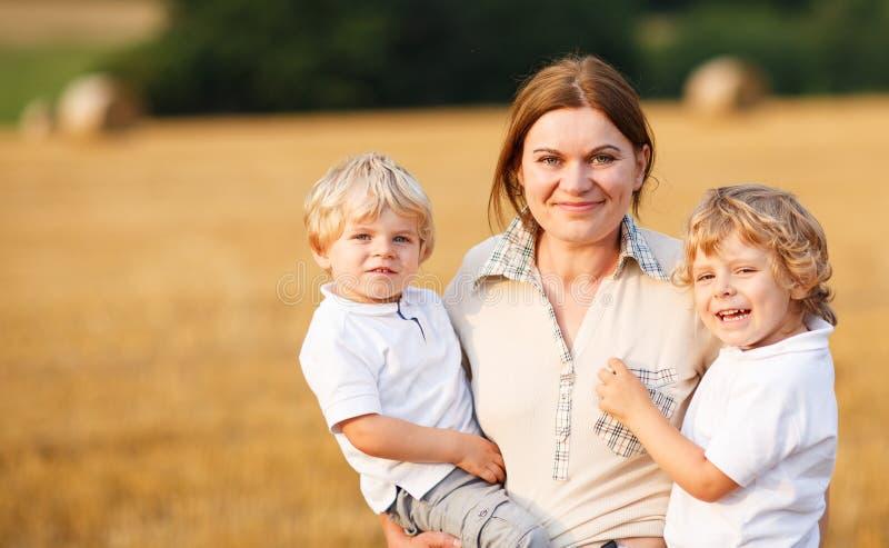 Молодая мать и 2 маленьких мальчика близнецов имея потеху на желтом сене стоковое изображение rf