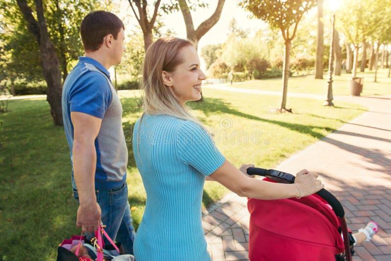 Молодая мать идя с детской дорожной коляской в парке стоковая фотография rf
