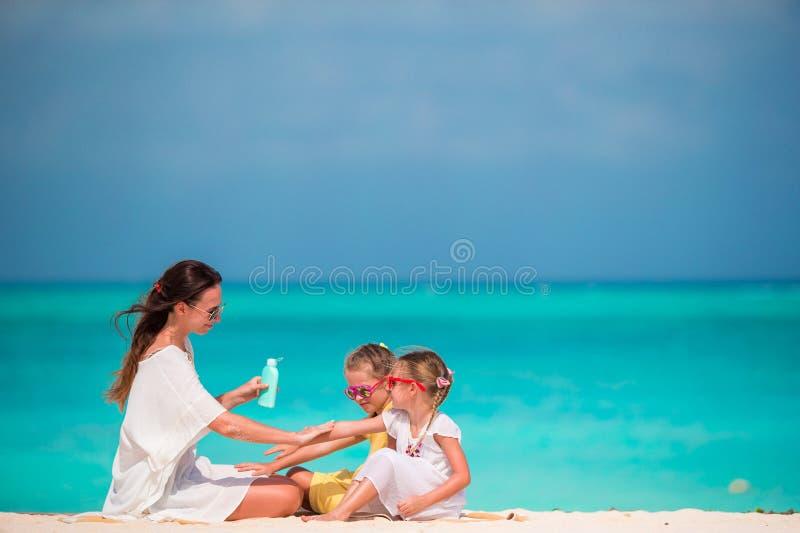 Молодая мать прикладывая солнцезащитный крем на ее детях стоковое изображение