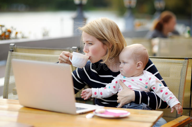 Молодая мать при ее младенец работая или изучая на ее компьтер-книжке стоковые фото