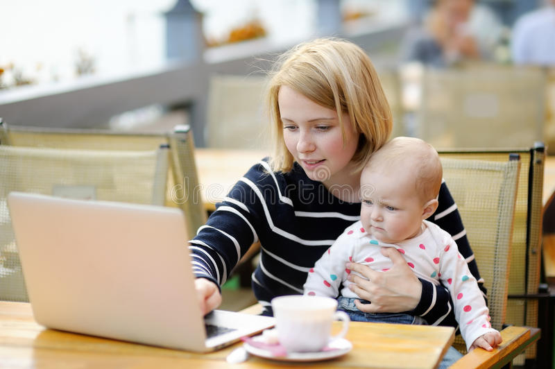Молодая мать при ее младенец работая или изучая на ее компьтер-книжке стоковые фотографии rf