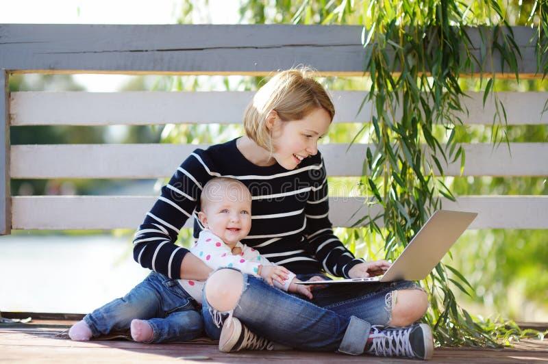 Молодая мать при ее младенец работая или изучая на компьтер-книжке стоковые изображения