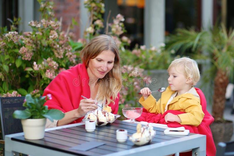 Молодая мать при маленькая дочь есть мороженое в кафе outdoors стоковая фотография