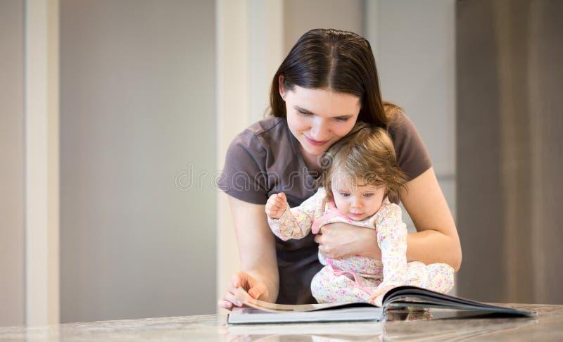 Молодая мать при маленький ребёнок читая поваренную книгу стоковые фото