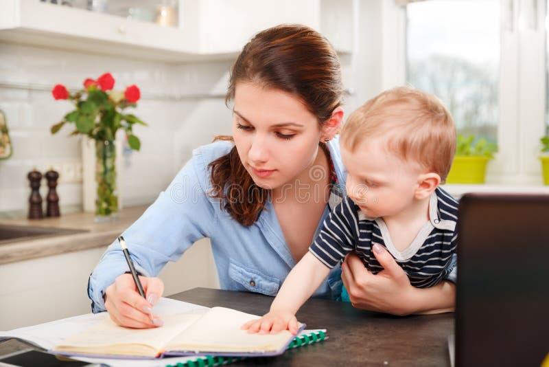 Молодая мать работая с ее младенцем стоковое фото rf