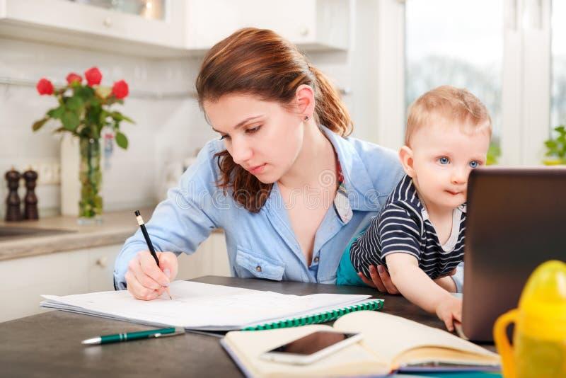 Молодая мать работая с ее младенцем стоковое изображение rf