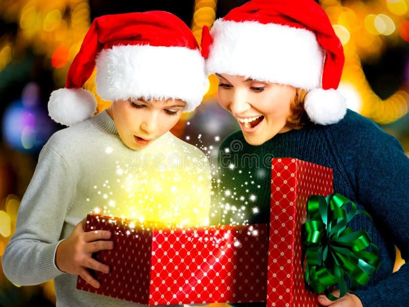 Молодая мать с ребенком раскрывает коробку с подарками на рождестве стоковые изображения rf