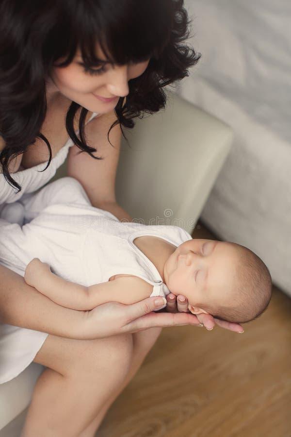 Молодая мать с спать младенцем в ее оружиях стоковые фото