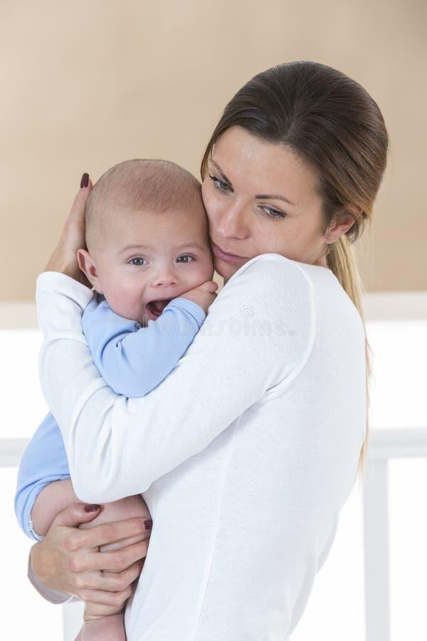 Молодая мать cheerfl держа ребёнок в ее оружиях стоковое изображение rf