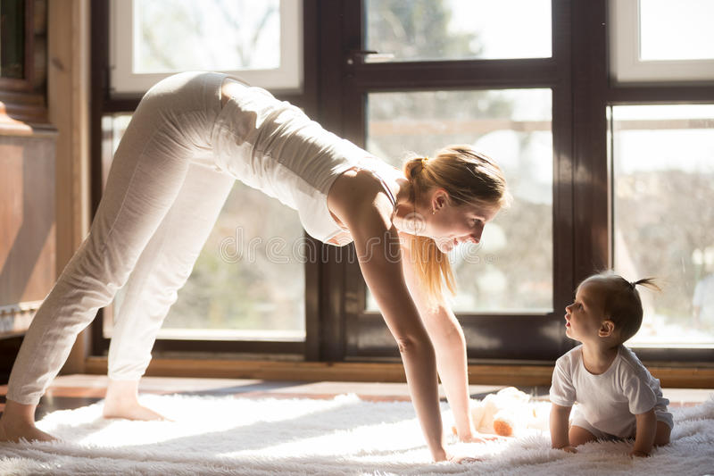 Молодая мать yogi и дочь младенца сидя близко, здоровый день стоковые фотографии rf