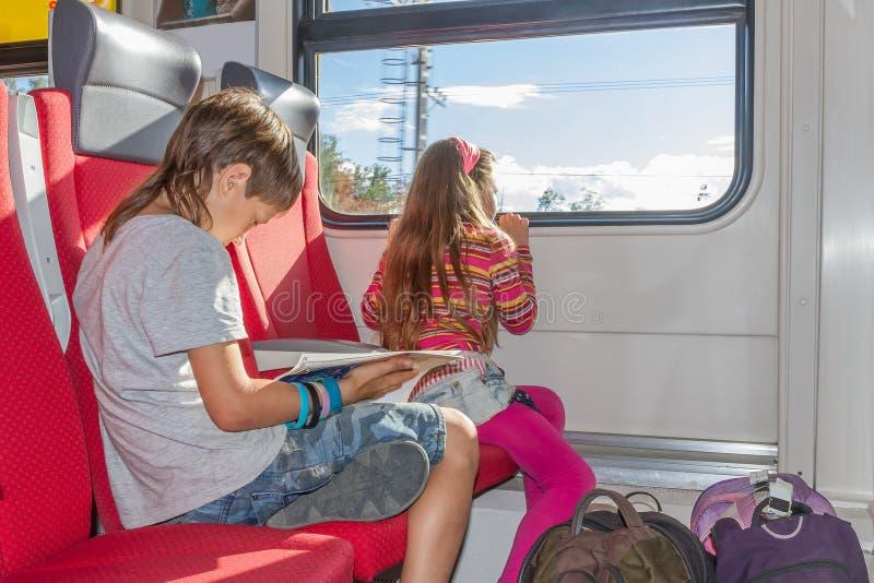 Молодая маленькая кавказская девушка путешествуя поездом стоковые изображения rf