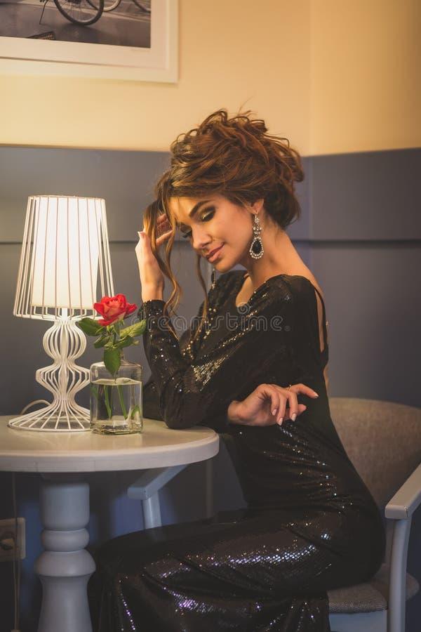 Молодая милая дама брюнет при вьющиеся волосы сидя в кафе стоковые фотографии rf