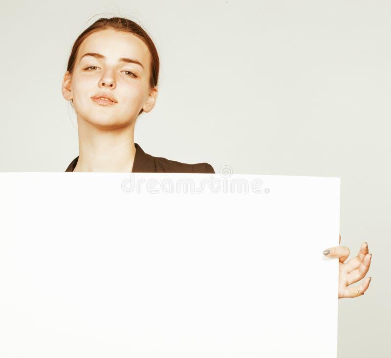 Молодая милая девушка брюнет с плакатом на студенте костюма дела белой предпосылки нося стоковое изображение