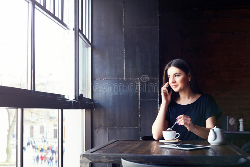 Молодая милая девушка говоря на телефоне в кафе стоковые изображения rf