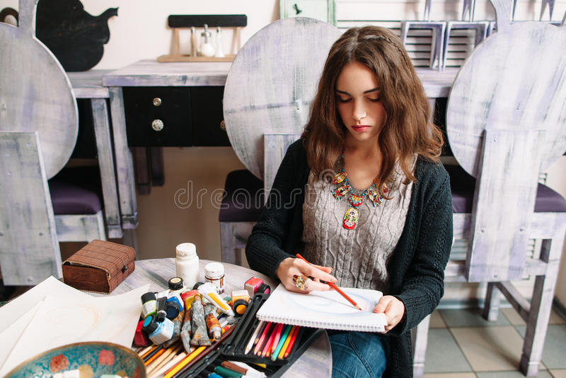 Молодая милая девушка чертежа на студии стоковая фотография
