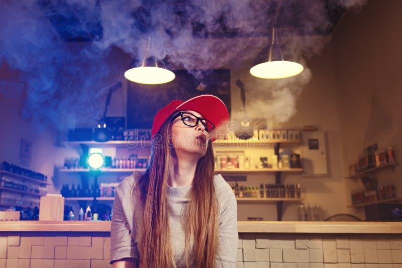 Молодая милая женщина в красном дыме крышки электронная сигарета на магазине vape стоковые изображения rf