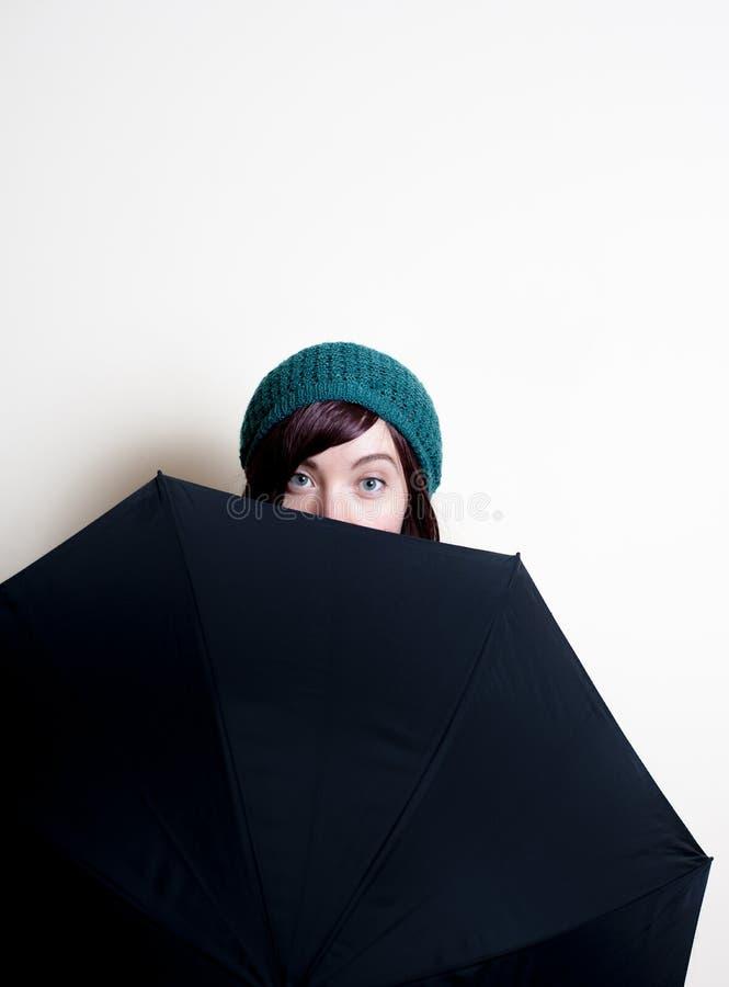 Молодая милая женщина при зеленая шляпа, усмехаясь наблюдает за зонтиком стоковые фотографии rf