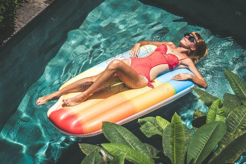 Молодая милая женщина при совершенное загоренное тело лежа на тюфяке воздуха в бассейне в лете и имея потеху Расслабляющее сексуа стоковое фото rf