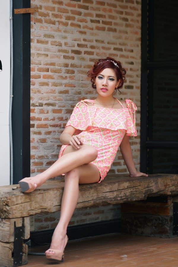 Молодая милая женщина сидя на деревянной скамье. стоковое фото